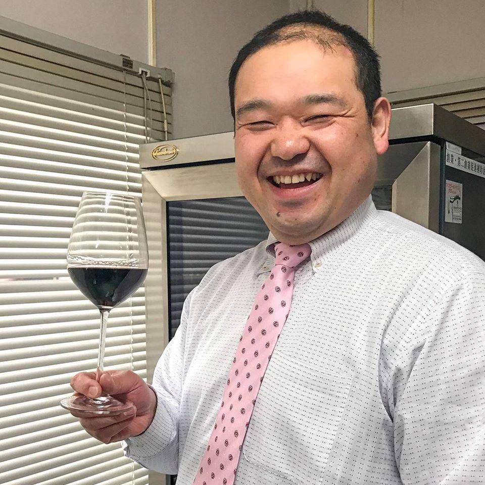 ワインを片手に笑顔を浮かべる弊社代表片吉慶太郎