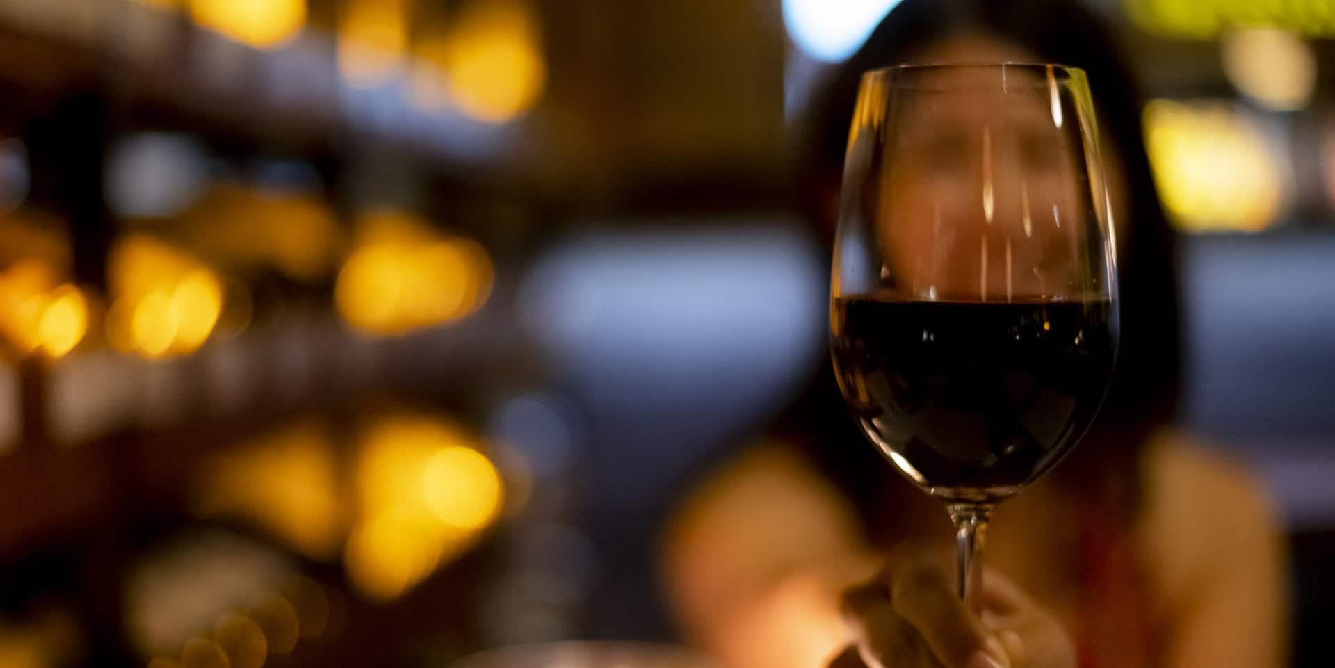 ワインが注がれたグラスと雰囲気のあるレストランの店内